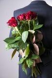 Mann mit Blumenstrauß von roten Rosen auf einem grauen Hintergrund Stockfotos