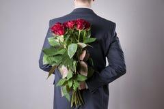 Mann mit Blumenstrauß von roten Rosen auf einem grauen Hintergrund Stockfotografie
