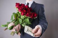 Mann mit Blumenstrauß von roten Rosen auf einem grauen Hintergrund Stockbilder