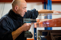 Mann mit Bohrmaschine-lochendem Loch auf einem klaren Kunststoffkoffer stockfoto