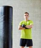 Mann mit Boxhandschuhen und Sandsack in der Turnhalle Stockbilder