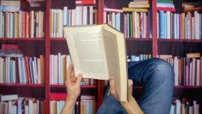 Mann mit Buch in der Hand das Lügen in der Universitätsbibliothek auf Bücherschrankhintergrund lesend stock video footage