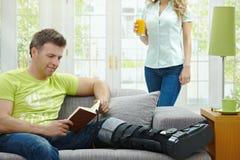 Mann mit Buch des gebrochenen Fahrwerkbeines Lese stockfotos
