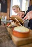 Mann mit Burger und Soße auf hölzerner Platte Stockfotos