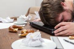 Mann mit Burnout schlafend auf seinem schmutzigen Schreibtisch Stockbild