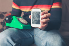 Mann mit defektem intelligentem Telefon und Drehtelefon Stockfotografie
