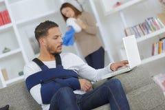 Mann mit dem Arm im Riemen unter Verwendung des Computerfrauenabstaubens stockfotos