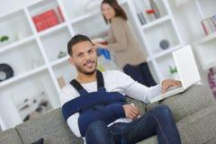 Mann mit dem Arm im Riemen unter Verwendung des Computers linkshändig stockbild