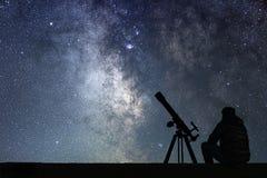 Mann mit dem Astronomieteleskop, das die Sterne betrachtet stockfoto