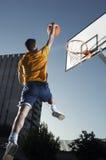 Mann mit dem Basketball, der in Richtung zum Band springt Stockbilder