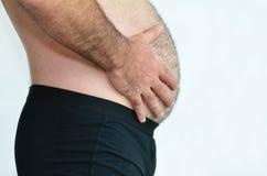 Mann mit dem Bauch, der sein Gewicht festsetzt Stockbild