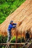 Mann mit dem blauen shiet, das auf der Bambustreppenherstellung steht, decken Dach mit Stroh Stockfotos