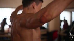 Mann mit dem bloßen Torso tut Übung mit Widerstandband backview stock footage