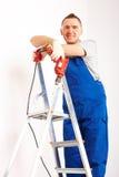 Mann mit dem Bohrgerät, das auf Strichleiter steht Stockbilder
