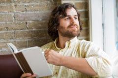 Mann mit dem Buch, das durch Fenster in Coffeeshop schaut Lizenzfreies Stockbild