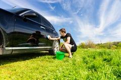 Mann mit dem Eimer, der schwarzes Auto auf dem Gebiet wäscht Stockfoto