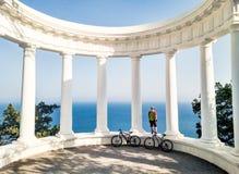 Mann mit dem Fahrrad, das auf Kolonnade steht stockfoto