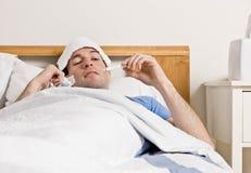 Mann mit dem Fieber, das in das Bett nimmt Temperatur legt Lizenzfreies Stockbild