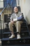 Mann mit dem gebrochenen Arm, der auf Treppe sitzt Lizenzfreies Stockfoto