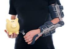Mann mit dem gebrochenen Arm, der Sparschwein zeigt Stockbilder