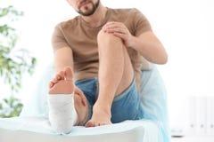 Mann mit dem gebrochenen Bein in der Form lizenzfreie stockbilder