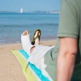 Mann mit dem Gips, der auf Strand sich entspannt Stockbilder