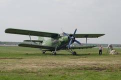 Mann mit dem grünen Flugzeugdoppeldecker AN2 auf der grünen Rollbahn stockfoto