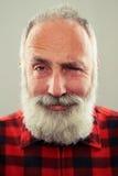 Mann mit dem grau-haarigen Bart, der Kamera und das Blinzeln betrachtet Lizenzfreie Stockbilder