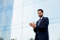 Mann mit dem guten Gefühl, das nahes Bürogebäude steht Lizenzfreies Stockbild