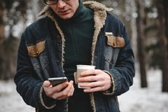 Mann mit dem Handygetränkkaffee im Freien Stockbild
