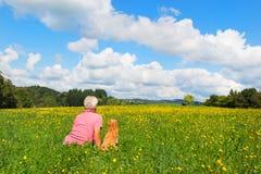 Mann mit dem Hund, der in der Landschaft sitzt stockfotos