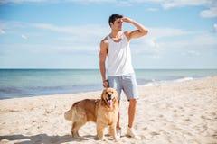 Mann mit dem Hund, der weit weg auf Strand steht und schaut Stockfoto