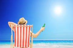 Mann mit dem Hut, der auf einem Strandstuhl sitzt und ein Bier nahe bei hält Stockbild