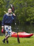 Mann mit dem Kajak-Paddel, das auf Gras steht Lizenzfreies Stockbild