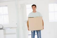 Mann mit dem Kasten, der in das neue Hauptlächeln sich bewegt Lizenzfreie Stockfotos