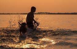 Mann mit dem kleinen Spürhundwelpen, der herum in der Ozeansonnenuntergangwelle täuscht Lizenzfreies Stockfoto