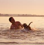Mann mit dem kleinen Spürhundwelpen, der herum in der Ozeansonnenuntergangwelle täuscht Lizenzfreie Stockfotos