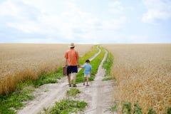 Mann mit dem Koffer und Jungen, die weg in Weizen gehen Stockfotos