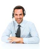 Mann mit dem Kopfhörer, der auf seinem Schreibtisch sich lehnt Stockbild