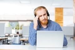 Mann mit dem Kopfhörer und Laptop, die unter Kopfschmerzen auf Arbeitsplatz leiden Lizenzfreies Stockfoto