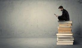 Mann mit dem Laptop, der auf Büchern sitzt Lizenzfreies Stockbild