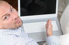 Mann mit dem Laptop, der auf Sofa sitzt Stockfoto