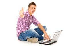 Mann mit dem Laptop, der sich Daumen zeigt Lizenzfreies Stockbild