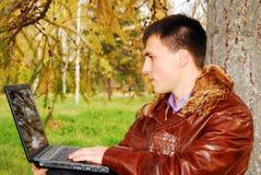 Mann mit dem Laptop im Freien. Stockbilder