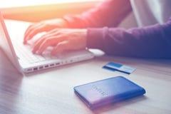 Mann mit dem Laptop, Pass und Kreditkarte, die das on-line-Einkaufen machen Stockfoto
