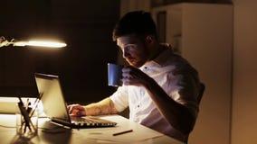Mann mit dem Laptop und Kaffee, die im Nachtbüro arbeiten stock video footage