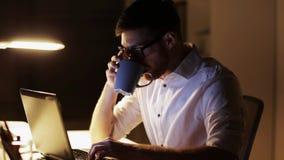 Mann mit dem Laptop und Kaffee, die im Nachtbüro arbeiten stock video