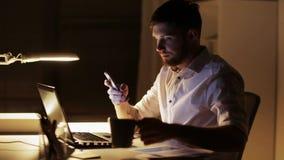 Mann mit dem Laptop und Smartphone, die im Nachtbüro arbeiten stock footage