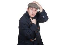 Mann mit dem Mantel, der Kappe hält Stockbild