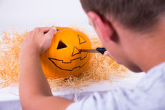 Mann mit dem Messer, das Kürbis für Halloween zubereitet Stockfotos